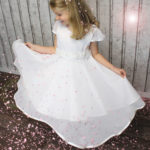 Kleine Flügelärmelchen und der wunderschöne Blumengürtel runden das Luxuskleid perfekt ab.